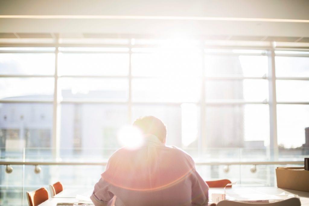 muz-sedici-v-kancelari-denni-svetlo